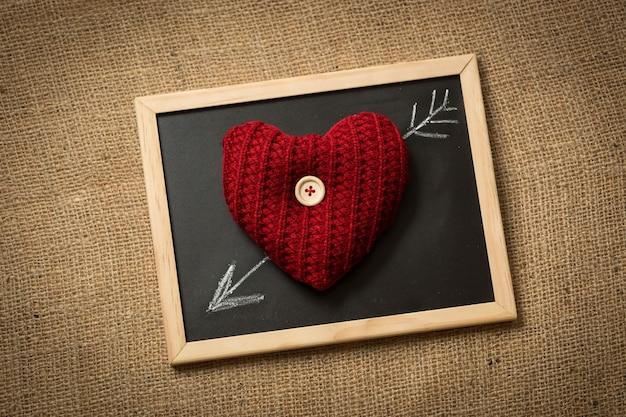 Primo piano del cuore a maglia sdraiato sulla lavagna con freccia disegnata