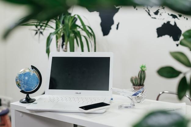 Primo piano del laptop e del globo nell'ufficio dell'agenzia di viaggi con piante