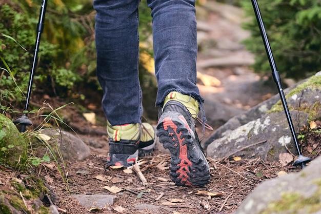 Gambe del primo piano in jeans e scarpe da trekking sportive durante un'escursione