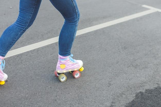 Primo piano delle gambe che indossano scarpe da pattinaggio a rotelle all'aperto