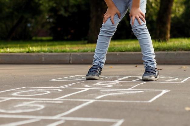 Primo piano delle gambe del ragazzino e della campana disegnata su asfalto. bambino che gioca a campana nel parco giochi all'aperto.
