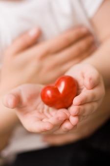 Primo piano di un bambino tra le braccia di una madre con un bel cuore rosso nelle sue mani