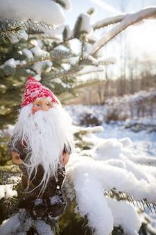 Primo piano piccolo babbo natale su un albero di natale sullo sfondo della neve e del sole splendente