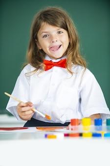Primo piano della piccola ragazza del bambino che disegna l'immagine con vernice colorata usando il pennello. educazione del bambino. concetto di arte e creatività dei bambini.