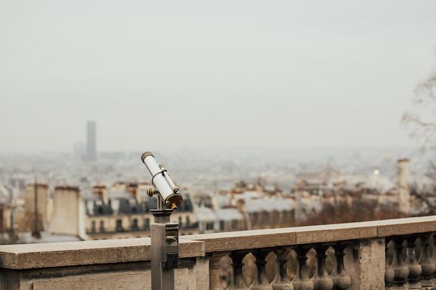Primo piano del binocolo di vedetta con vista sopra l'orizzonte urbano del paesaggio urbano di parigi