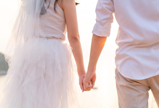 Primo piano delle coppie amorose che tengono le mani