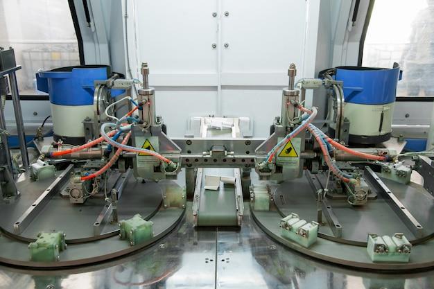 Primo piano della macchina per la fabbricazione e il montaggio di cerniere per porte e finestre