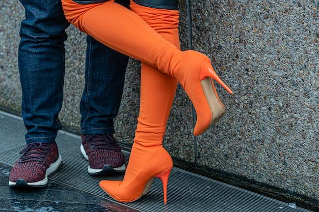 Il primo piano delle gambe maschii e femminili durante una data, la donna solleva allegro il vantaggio, concetto di relazione