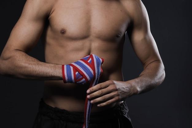 Mano maschio del combattente del primo piano con le bende. pugni del combattente serrati prima di un combattimento o di un allenamento in una palestra sportiva.