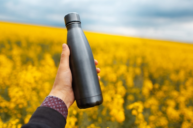 Primo piano della mano maschile che tiene una bottiglia di metallo riutilizzabile grigio scuro sullo sfondo di un campo di colza sfocato con spazio per le copie.