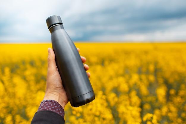 Primo piano della mano maschile che tiene una bottiglia d'acqua termica riutilizzabile in acciaio grigio scuro sullo sfondo di un campo di colza sfocato.