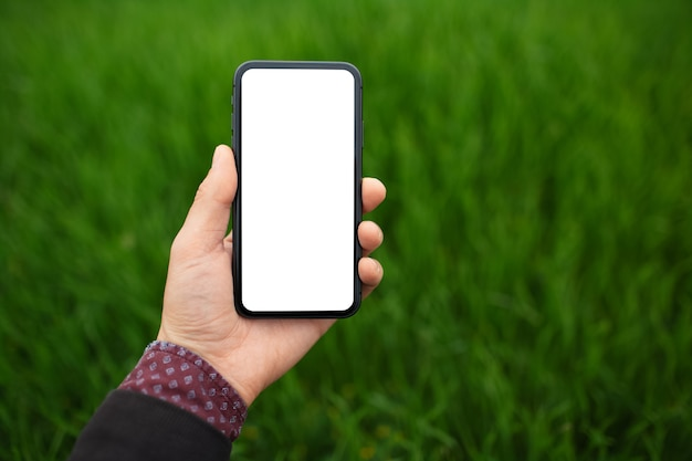Primo piano dello smartphone maschio della tenuta della mano con il modello su fondo di erba verde vaga con lo spazio della copia.
