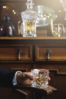 Primo piano della mano maschio con un bicchiere di whisky costoso