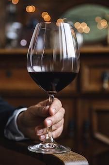 Primo piano della mano maschio con un bicchiere di vino rosso
