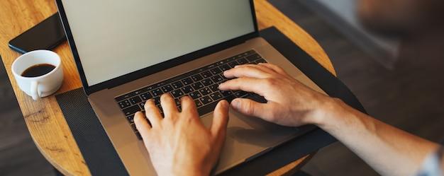Primo piano delle mani maschili che digitano sul computer portatile sul tavolo di legno vicino alla tazza di caffè e all'insegna panoramica dello smartphone, vista dall'alto.