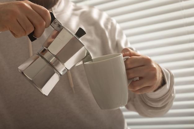 Primo piano del maschio versando caffè in ufficio il giorno d'estate concetto di tonificante mattina e positivo