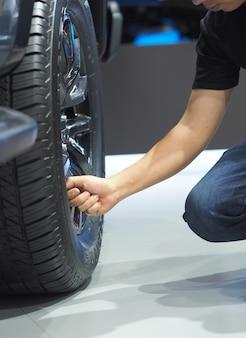 Mano dell'uomo del primo piano che controlla la grande ruota della nuova auto