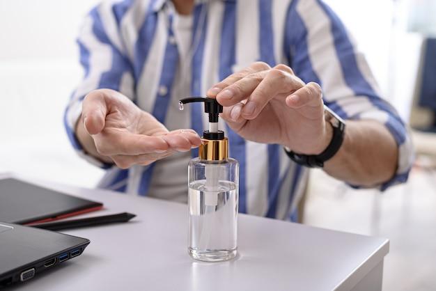 Primo piano man mano che pulisce con disinfettante, pulizia gel antibatterico per le mani, lavoro a distanza sul computer portatile a casa concetto