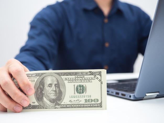 Mano dell'uomo del primo piano che tiene il dollaro dei soldi sul tavolo con il colpo del raccolto del computer portatile