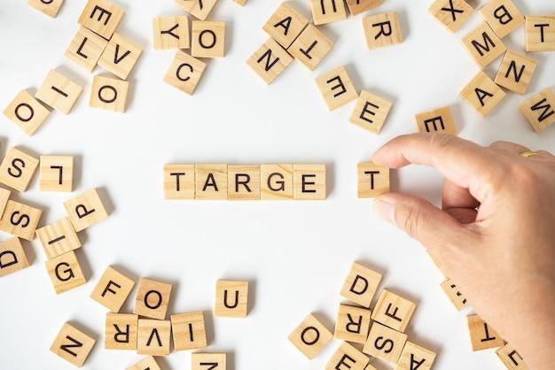 Primo piano della mano dell'uomo che tiene il blocchetto di legno della lettera di t per completare la dicitura target con altri blocchi di lettere inglesi.