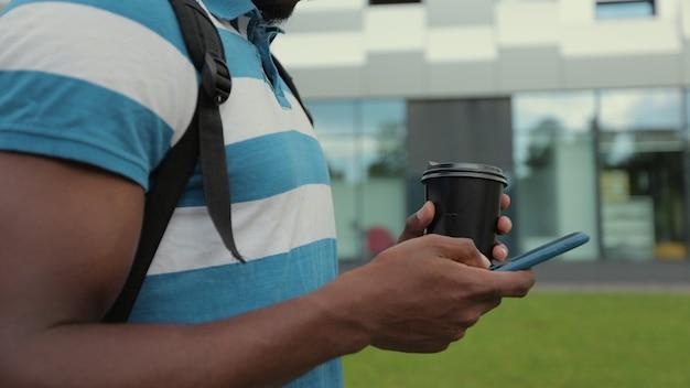 Primo piano di una mano dell'uomo che utilizza smartphone nella comunicazione online della città con gli amici che digitano messaggi di chat ricerca su internet internet
