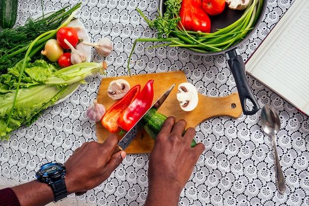 Primo piano dell'uomo mani afroamericano tagli verdure friggere insalata pepe, funghi, pomodoro in cucina ricettario sul tavolo .vegan cibo sano.