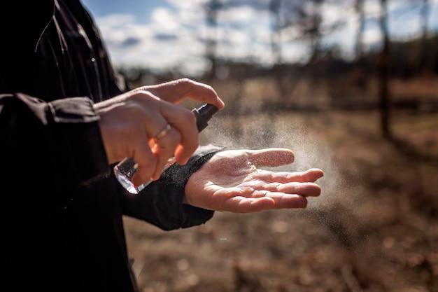 Le mani dell'uomo del primo piano che applicano lo spruzzo dell'alcool o l'anti spruzzo dei batteri per impedire la diffusione del virus