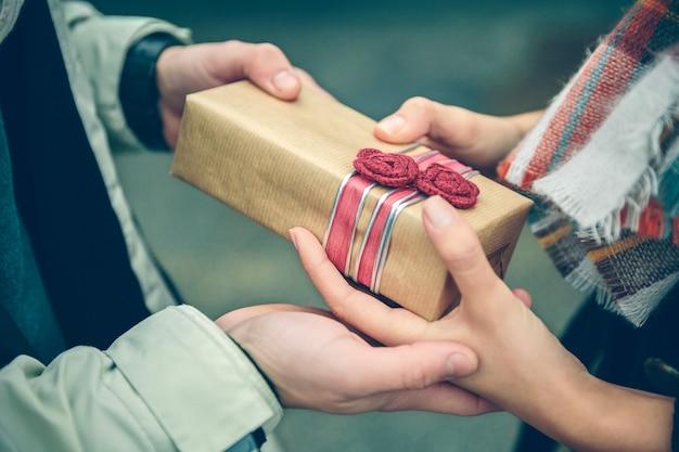 Primo piano delle mani dell'uomo che danno una confezione regalo con fiori rossi fatti a mano a una donna con sciarpa in una fredda giornata autunnale. amore e concetto di relazioni di coppia.
