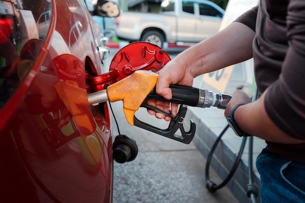 Le mani dell'uomo del primo piano gestiscono lo strumento per il rifornimento della pompa di benzina nell'auto rossa, il lavoro della stazione di servizio