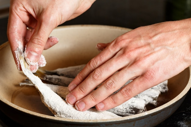Primo piano delle mani dell'uomo mettere l'odore di pesce fresco nella farina sulla padella. cibo malsano sull'olio