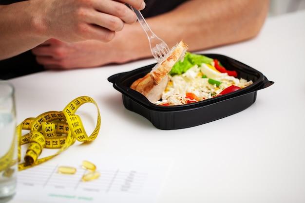 Primo piano di un uomo che tiene una scatola piena di alimenti ricchi di proteine per l'alimentazione sportiva