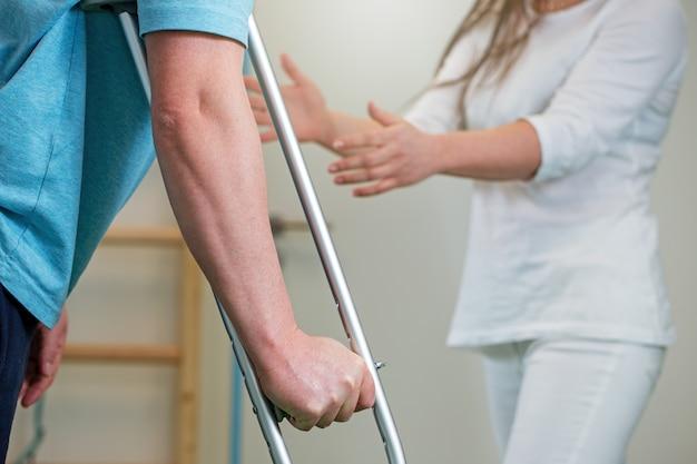 Primo piano dell'uomo che tiene la stampella durante la riabilitazione con il fisioterapista della donna