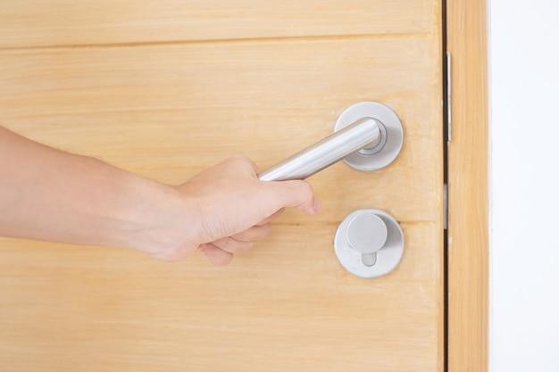 Uomo del primo piano che tiene la maniglia della maniglia della porta di legno tra aprire o chiudere la porta