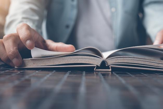 Primo piano dell'uomo che legge un libro sul tavolo