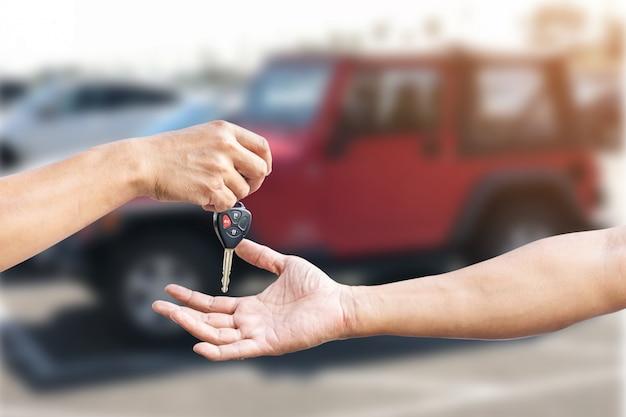 Primo piano la mano di un uomo sta consegnando una chiave dell'auto alla mano di un altro uomo, utilizzare per il concetto di industria di riparazione auto, assicurazione o commercio di automobili.