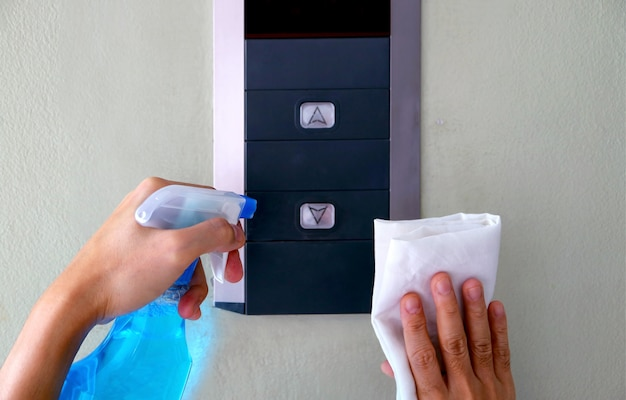 Mani dell'uomo del primo piano che puliscono il pannello dell'elevatore, prevenzione di covid-19