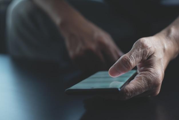 Primo piano dell'uomo che utilizza il dito del telefono cellulare che tocca sullo schermo vuoto
