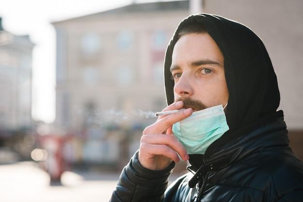 Uomo del primo piano con la maschera durante la pandemia covid-19 che fuma una sigaretta alla via.
