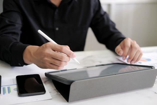 Uomo del primo piano con la penna dello stilo che scrive sul blocco note digitale, toccante sullo schermo della compressa digitale che lavora al computer portatile in ufficio. web designer che lavora al suo progetto. affari senza carta, tecnologia