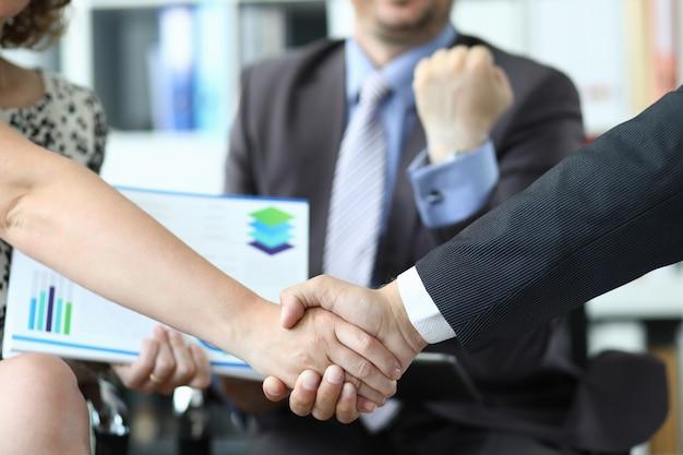 Primo piano di un uomo e di una donna che si stringono la mano davanti a un uomo sorridente con i documenti