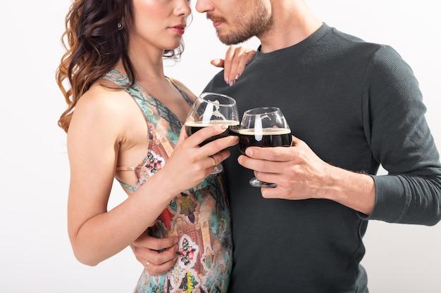 Primo piano di un uomo e di una donna che tostano con bicchieri di birra scura sul muro bianco. concetto di oktoberfest.
