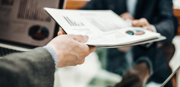 Il primo piano del direttore delle finanze prende il rendiconto finanziario dal dipendente sul posto di lavoro in ufficio