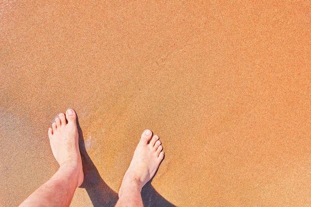 Il primo piano dei piedi nudi dell'uomo sta al bagnato sulla vacanza della spiaggia sul piede della spiaggia dell'oceano sull'atmosfera di estate dello spazio vuoto della copia della sabbia del mare
