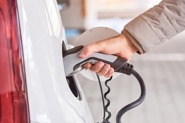 Primo piano equipaggia la mano che tiene la ricarica dell'auto elettrica collegata all'auto elettrica alla stazione di ricarica pubblica. veicolo rispettoso dell'ambiente e a zero emissioni.