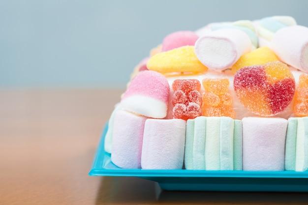 Primo piano di marshmallow e torta di fagioli di gelatina su un piatto blu per una festa per bambini, in tenui toni pastello