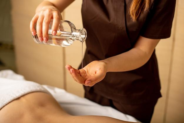 Primo piano delle mani del massaggiatore versando olio aromatico sulla schiena della donna