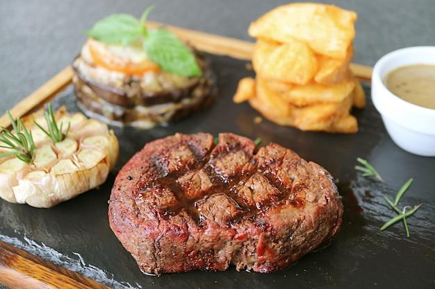 Primo piano di una bistecca di filetto mignon mediamente ben grigliata con verdure grigliate su piastra di pietra calda hot