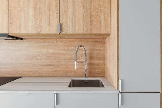 Primo piano del lavandino e del rubinetto del metallo alla mobilia di legno della cucina minima contemporanea alla ristrutturazione vuota...