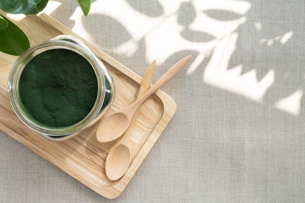 Primo piano di microscopiche alghe blu-verdi - polvere di spirulina in un barattolo di vetro, è un eccellente integratore alimentare per dieta vegana, vegetariana o vegetale perché contiene multivitaminici tra cui b12.