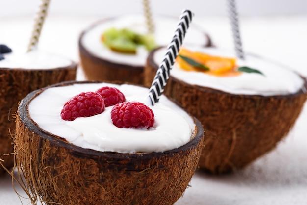 Primo piano frappè con frutti di bosco e tubi in ciotole di cocco su bianco